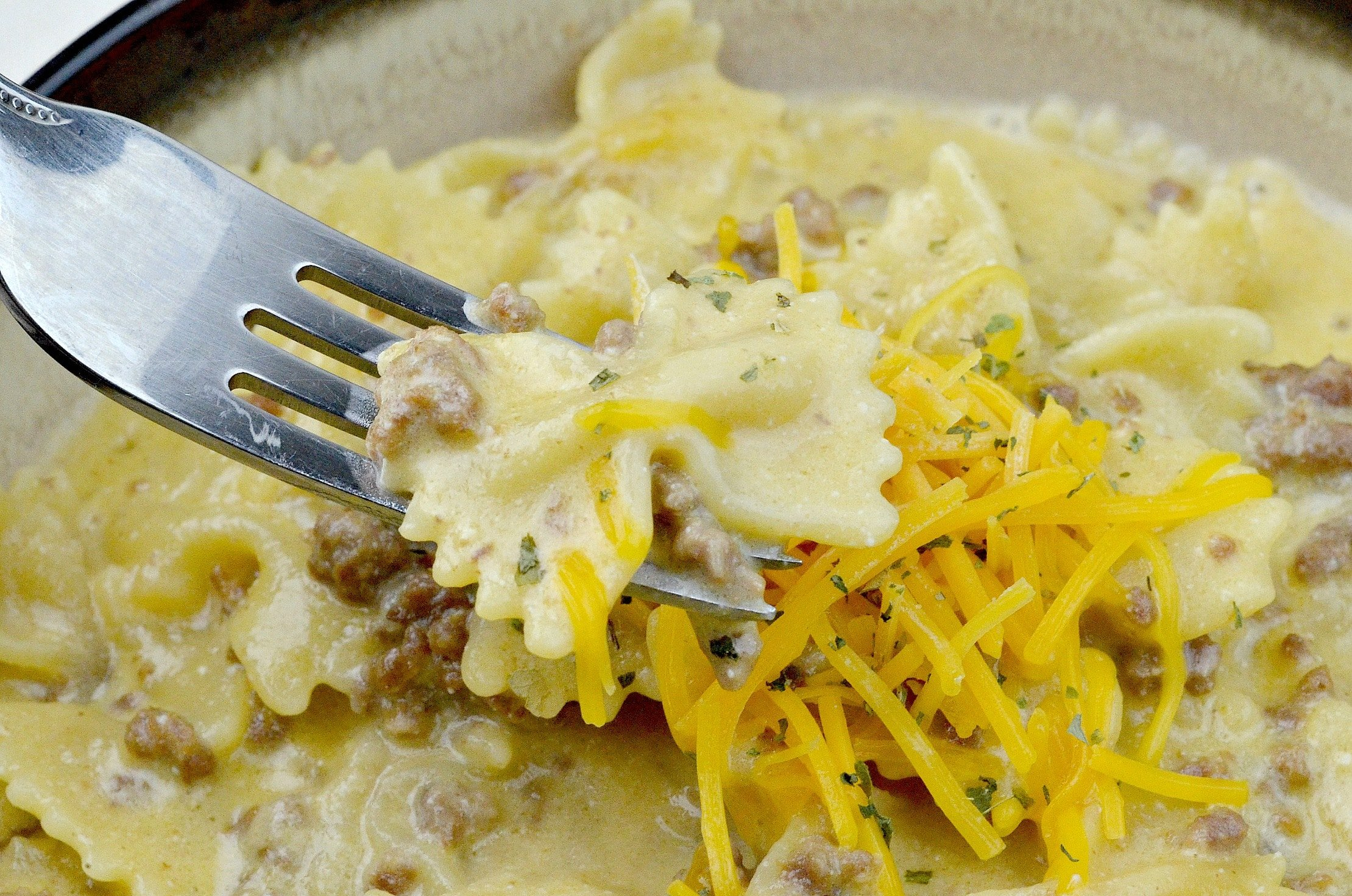 Copycat Hamburger Helper Cheddar Melt Closeup On Fork. This creamy and delicious Pressure Cooker Copycat Hamburger Helper Cheddar Melt will knock your families socks off and keep them coming for more.