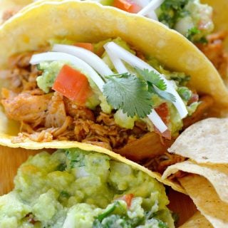 A tasty Chicken Tacos with a Homemade Guacamole recipe, featuring fresh toppings and a side of tortilla chips. Make this easy chicken taco and homemade guacamole recipe for the perfect taco Tuesday dinner.
