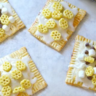 Homemade Honeycomb Cereal Pop-Tarts that are stuffed with apple butter and topped with homemade vanilla icing. Think Biggerer and be Back To School Ready with these easy homemade hand pies that you can stuff and top with your favorite flavors.