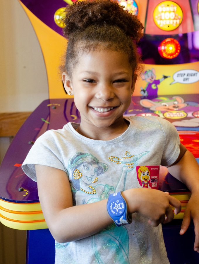 Chuck e cheeses VIP birthday Party with an African American birthday girl wearing a star wristband. Each Birthday Star Wristband gives the user 2 hours of unlimited play.