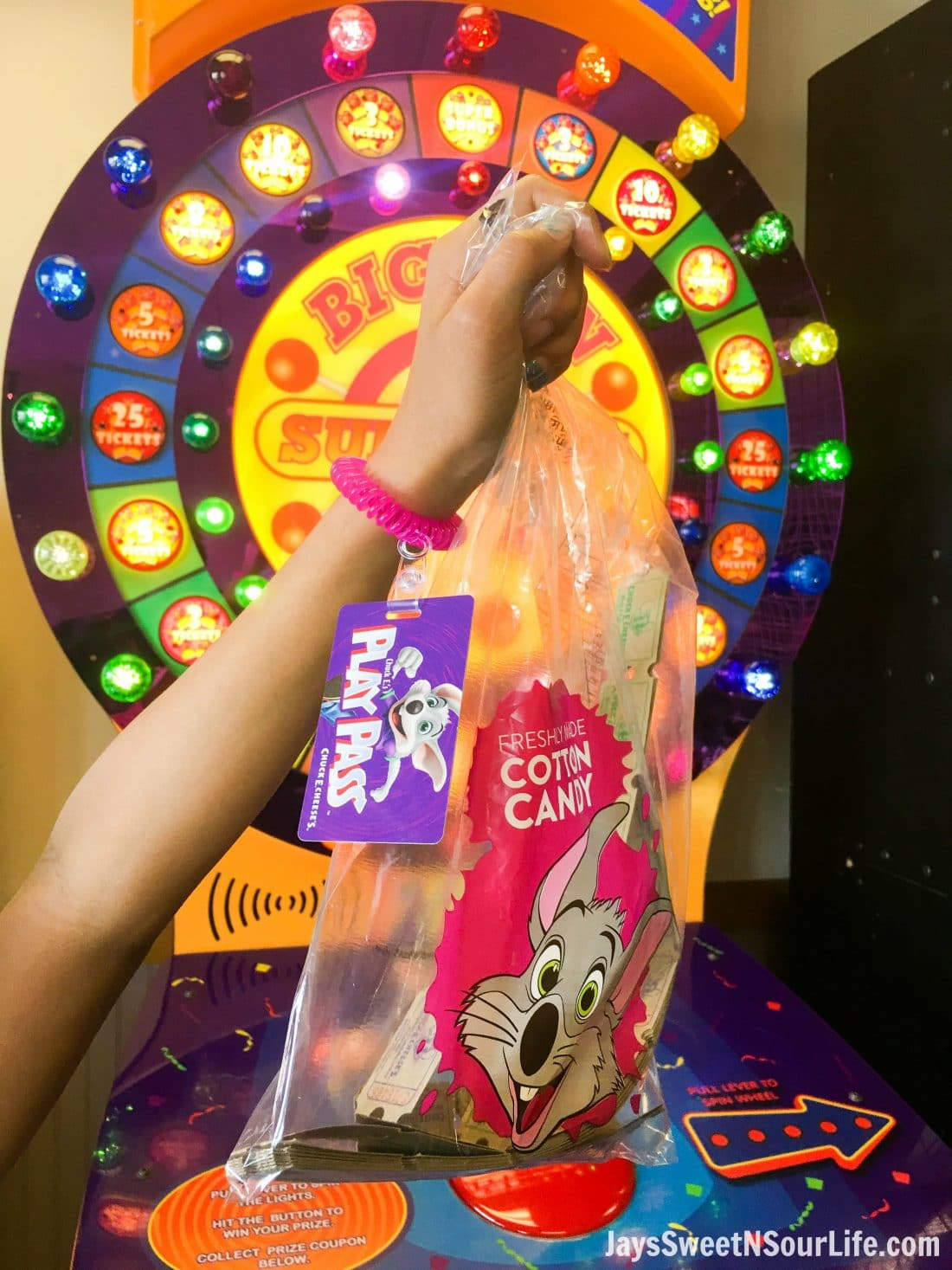 Chuck e cheeses VIP birthday Party Play Pass with wrist band, holding a bag of tickets. Book your party today and have guests enjoy 2 hours of unlimited game play.