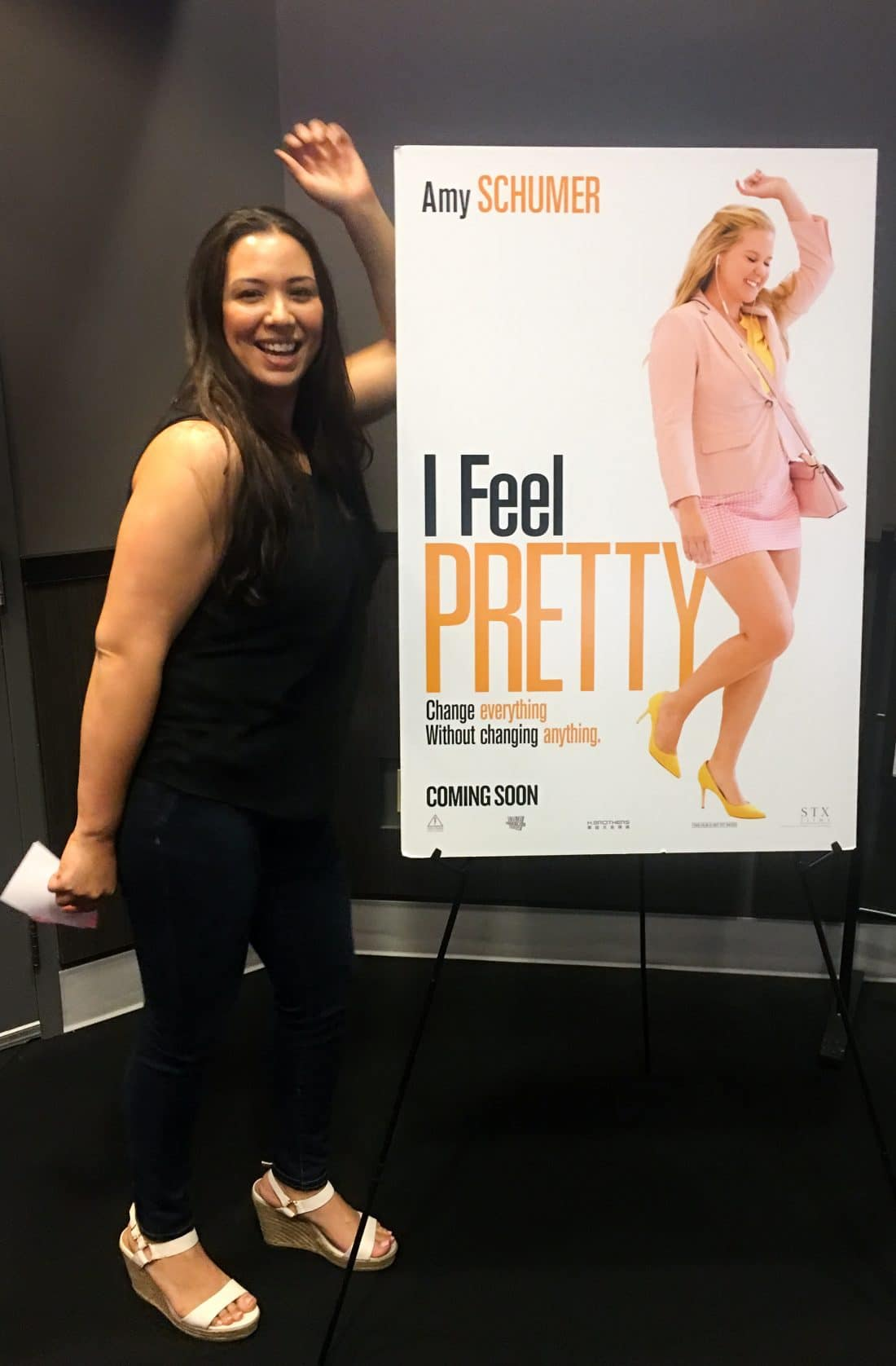 Filipino Woman standing in front of I Feel Pretty Movie Poster. The I Feel Pretty Film is in theaters everywhere today.