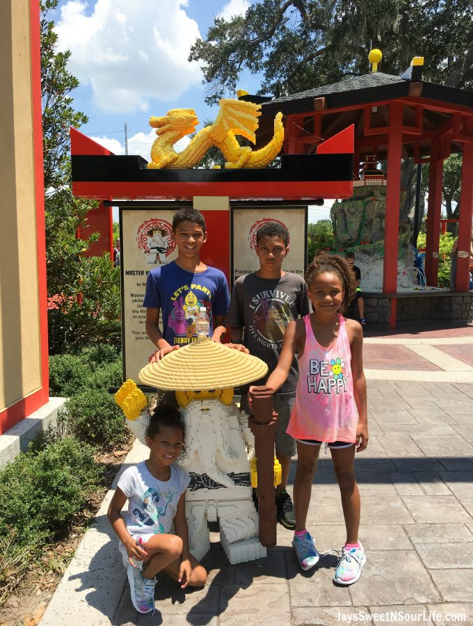 African American family at Legoland Florida Ninjago World snapping a Character Photo with Master Wu. Spend your summer building memories at Legoland in Florida. There is something for the whole family to enjoy at this wonderful Theme Park.