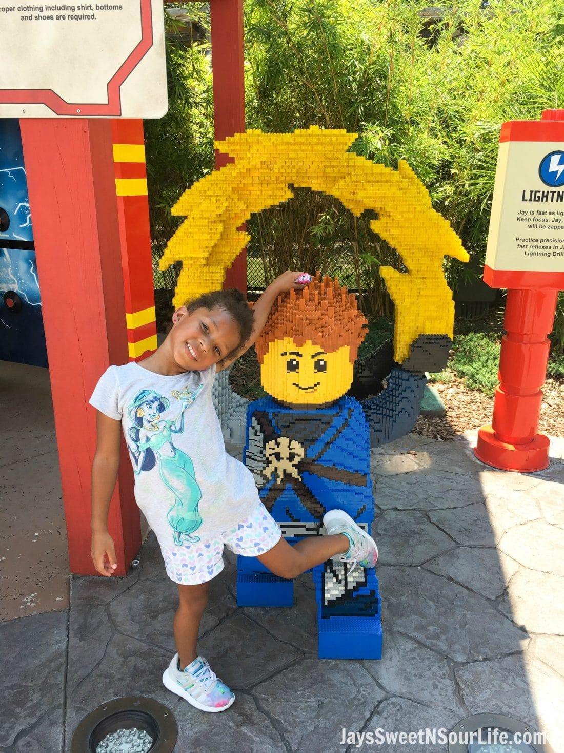 African American girl at Legoland Florida Ninjago World snapping a Character Photo. Spend your summer building memories at Legoland in Florida. There is something for the whole family to enjoy at this wonderful Theme Park.