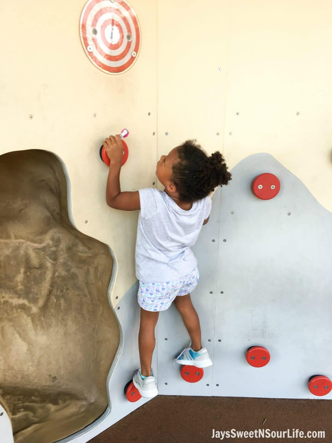 African American girl scaling the walls at Legoland Florida Ninjago World Coles Rock Climb. Spend your summer building memories at Legoland in Florida. There is something for the whole family to enjoy at this wonderful Theme Park.