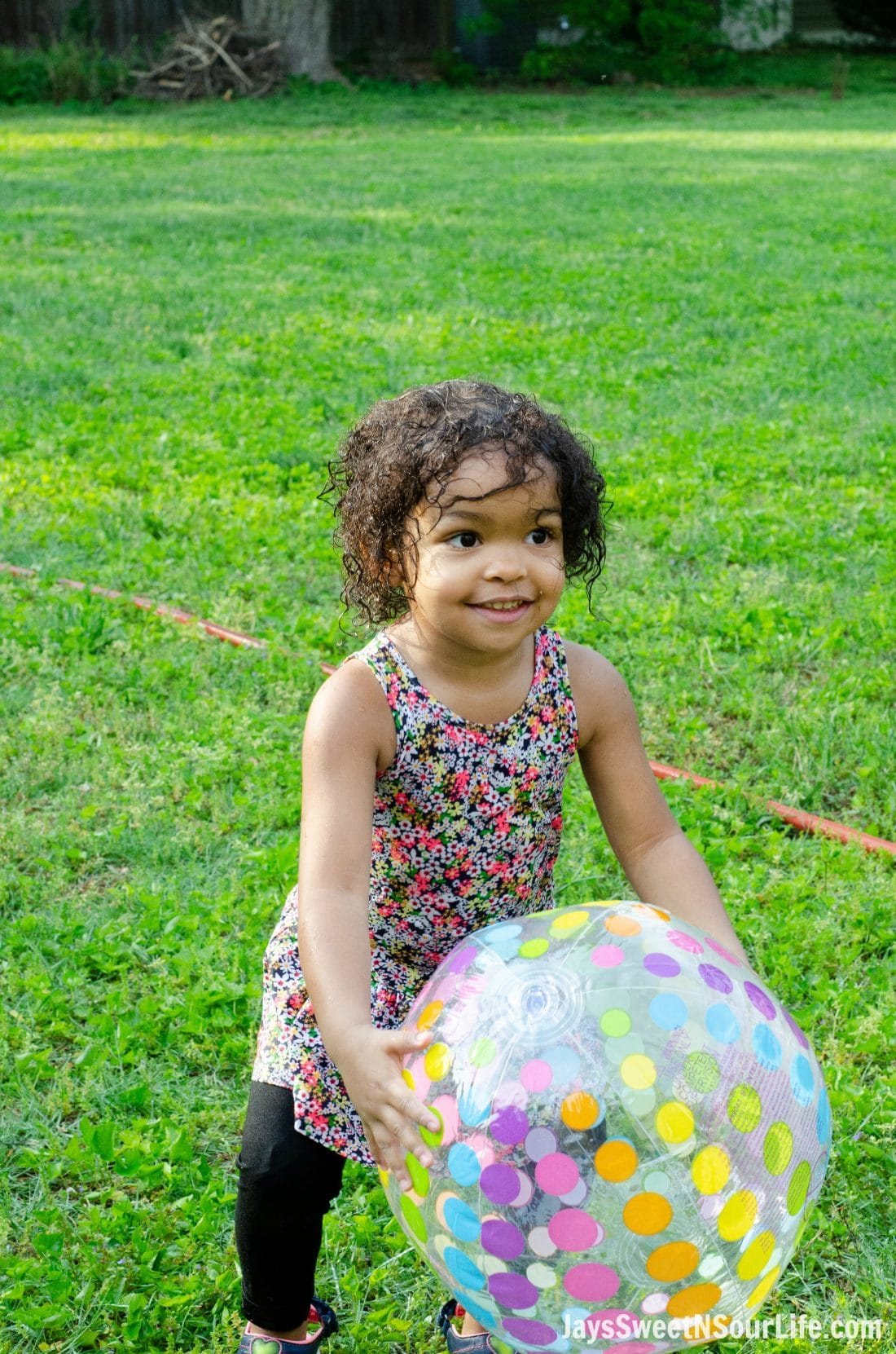 Little african american girl playing with a beach ball at a Beach Sundae Party.