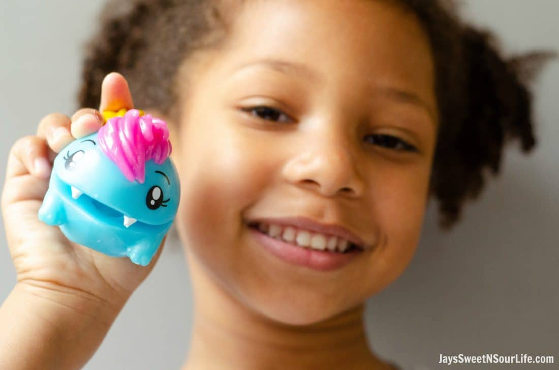 African American girl holding Pooparoos squishy toy. Pooparoos are full of fun surprises and tons of fun for all.