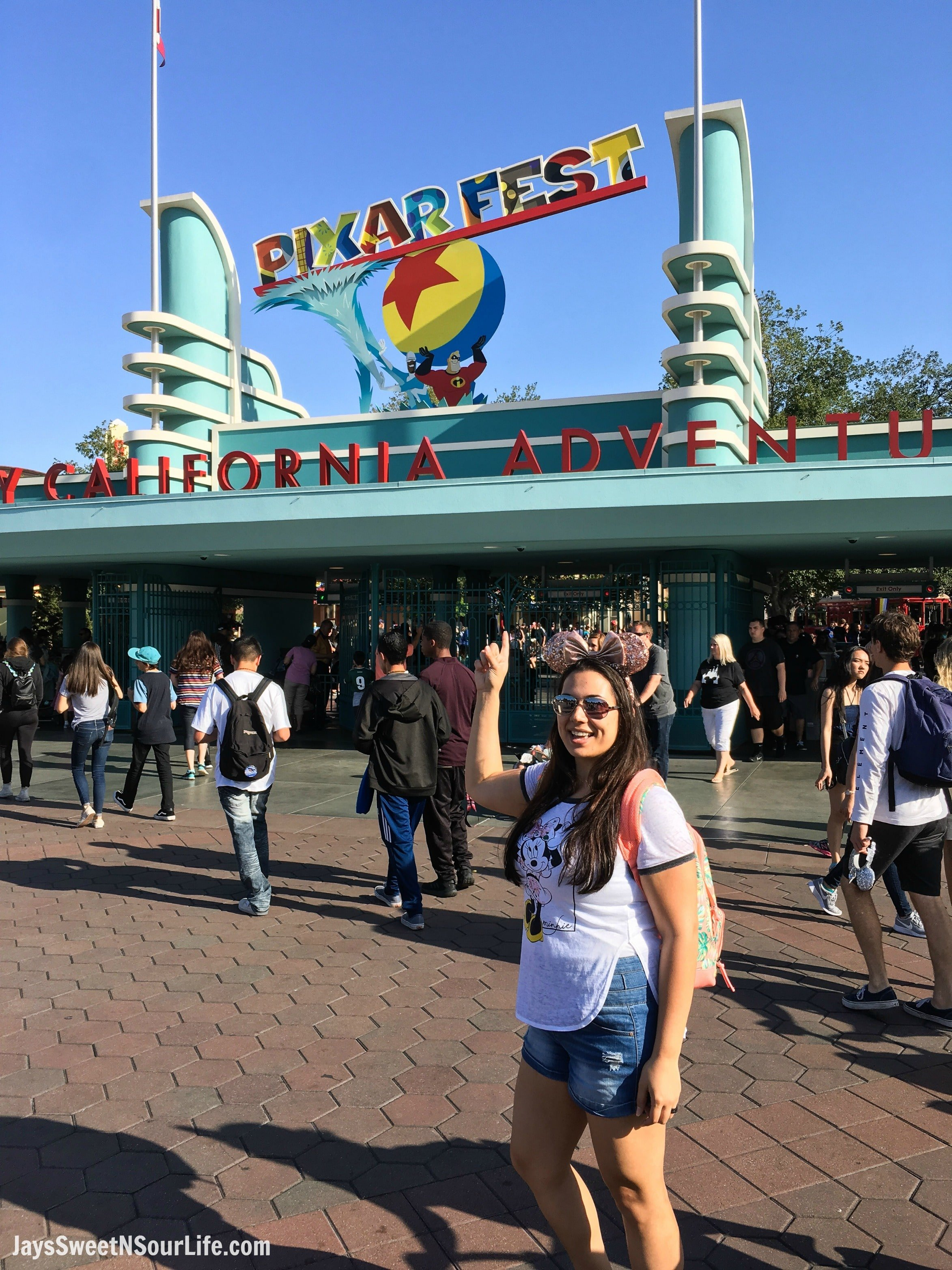 Pixar Fest at Disneyland Filipino Woman Pointing To Sign. Pixar Fest at Disneyland runs from April 13 through September 3rd.
