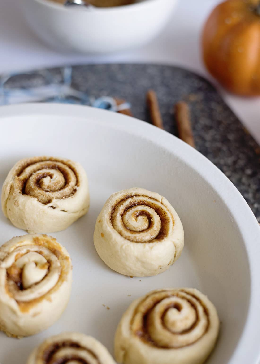 Pumpkin Spice Cinnamon Rolls Closeup In Pan Bake. Fill your home with the delicious smell of these easy to make Pumpkin Spice Cinnamon Rolls.