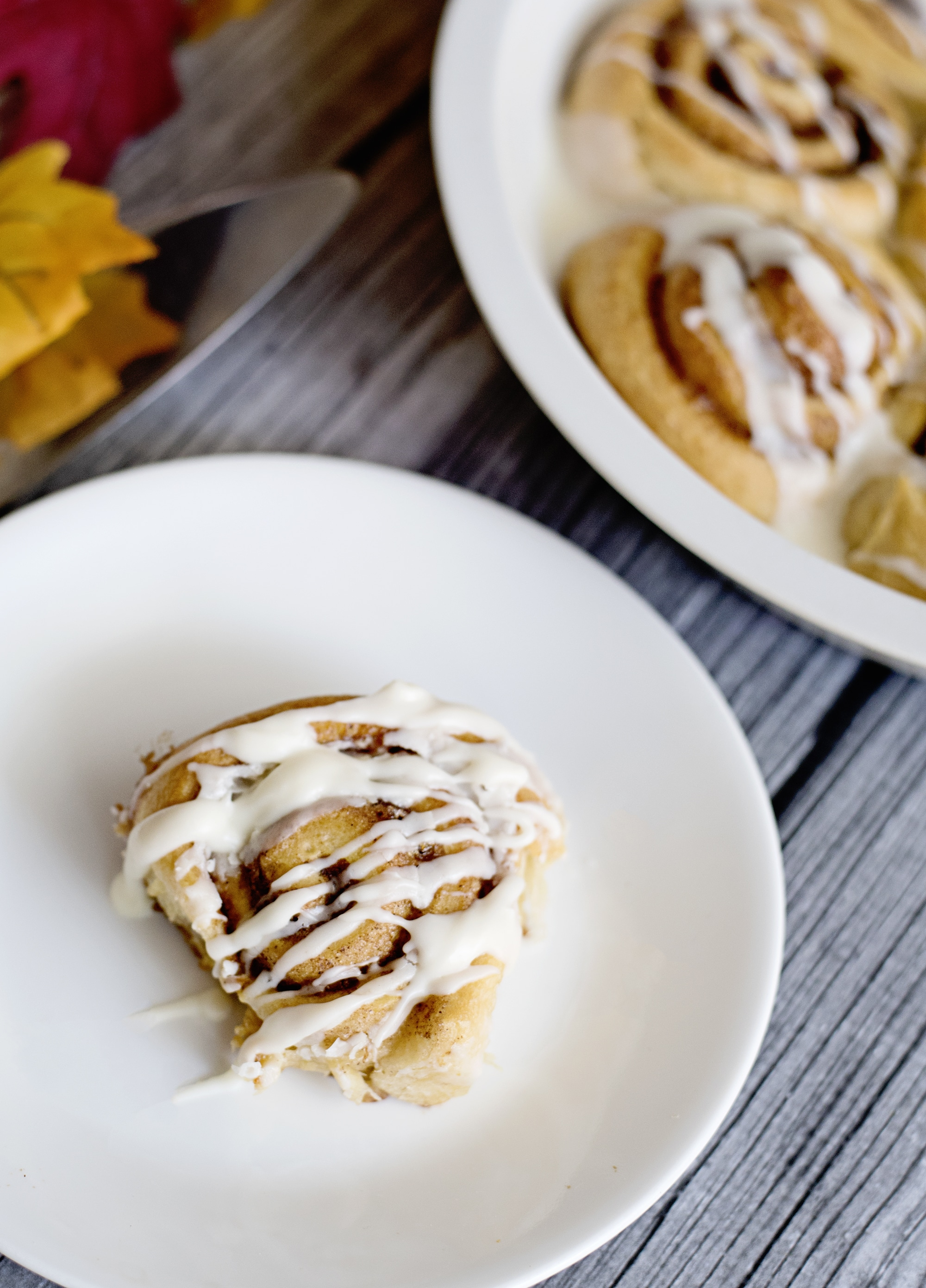 Pumpkin Spice Cinnamon Rolls On Plate. Fill your home with the delicious smell of these easy to make Pumpkin Spice Cinnamon Rolls.