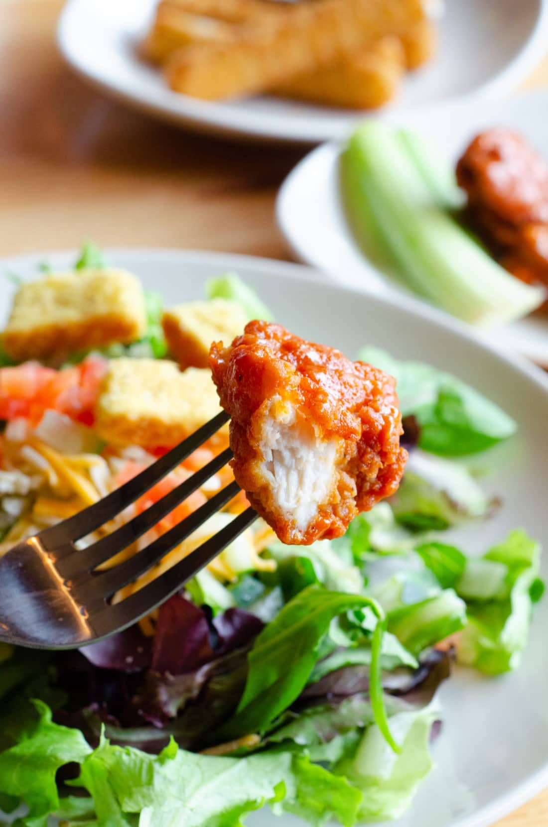 Buffalo Chicken on fork in front of Garden Salad at Applebee's. Take advantage of the Applebee's Delicious New Three-Course Meal's Starting at $12.