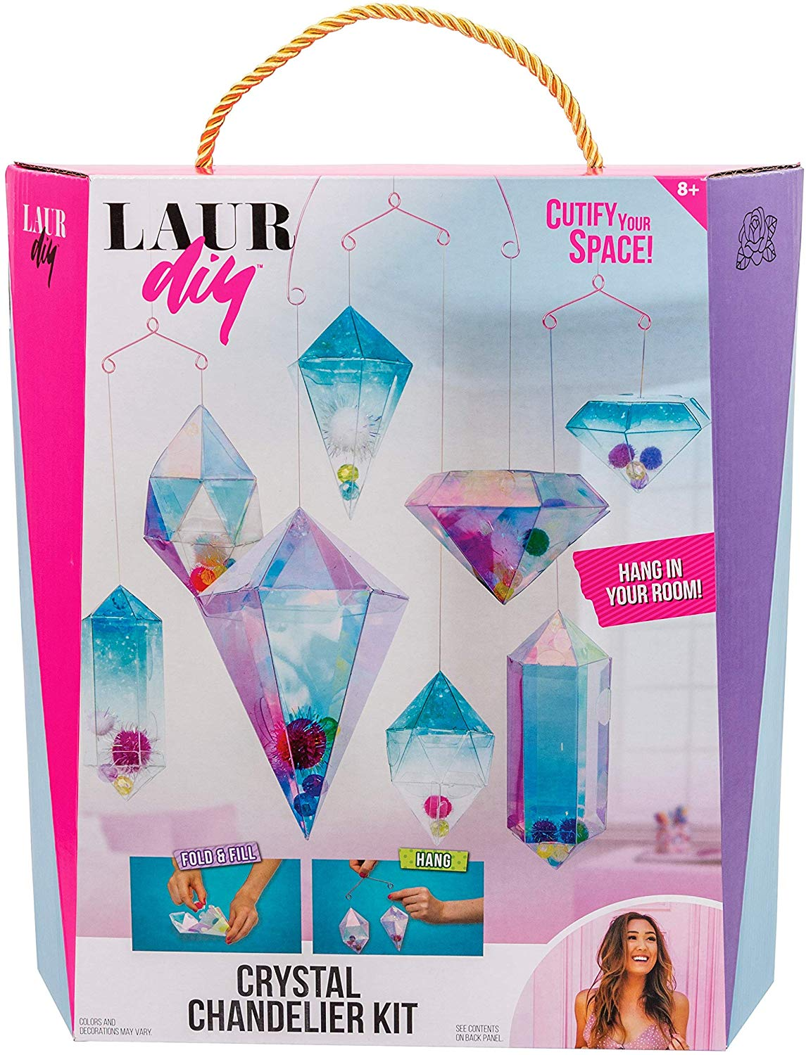 """Rose Art LaurDIY Crystal Chandelier Kit Introducing LaurDIY craft kits inspired by Lauren riihimaki's crafty tutorials, life hacks, and room decor ideas on YouTube. Now you can bring her style home with the LaurDIY crystal chandelier kit! At-home designers fold eight shapes to construct the hanging """"crystals"""", decorate them with pom poms and beads, then connect the crystals to form an incredible, iridescent, chandelier. This comprehensive kit includes 8 crystal shapes, 5 hangers, 40 pom poms, 32 iridescent beads, nylon string, a clip and connecting link, and an easy-to-follow guide with step-by-step instructions and images."""