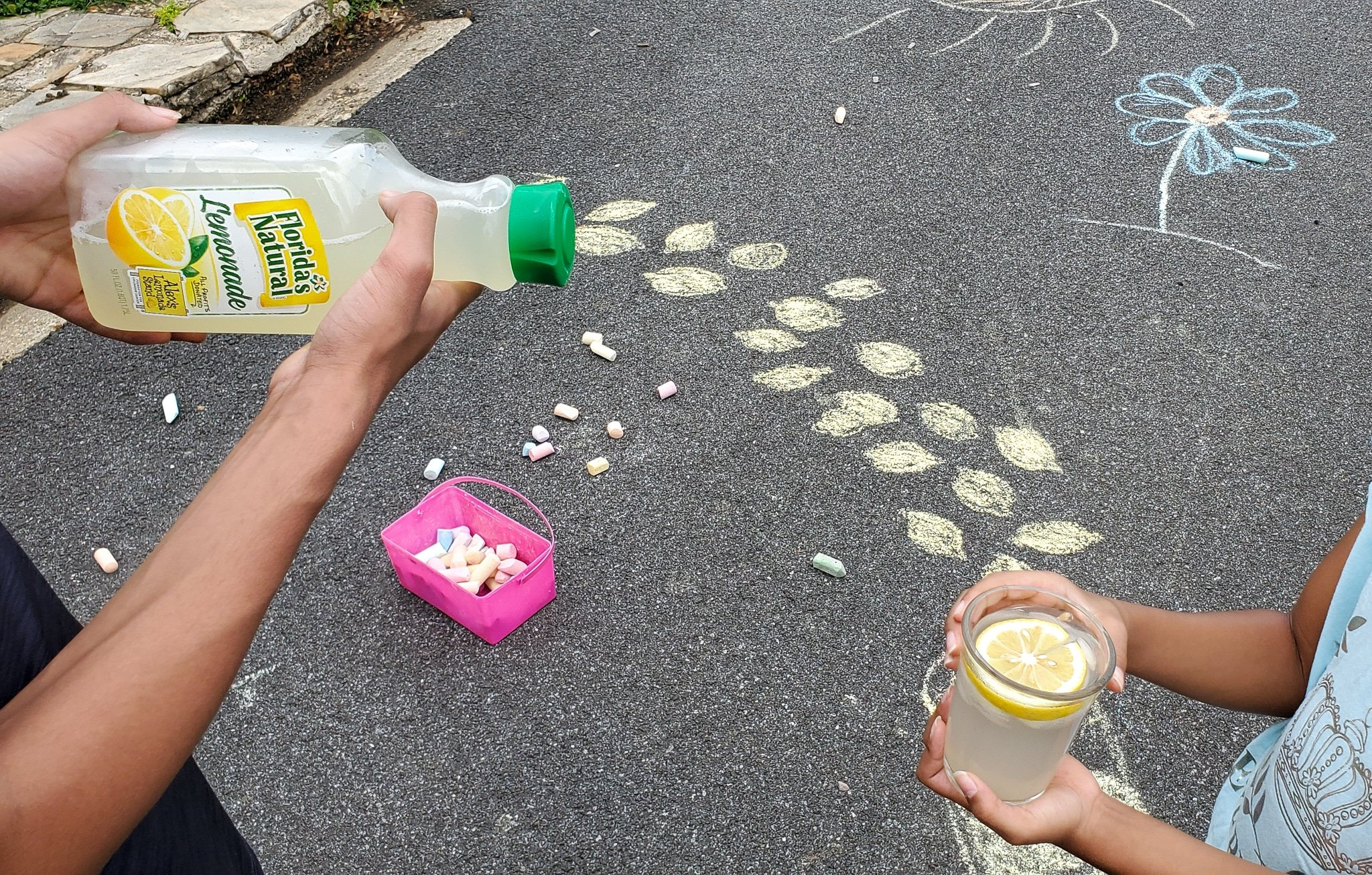 Lemonade Art Pouring Into Glass. Looking for a fun way to keep the kids entertained this summer? Celebrate the start of summer with Lemonade-Inspired Art In the Backyard.