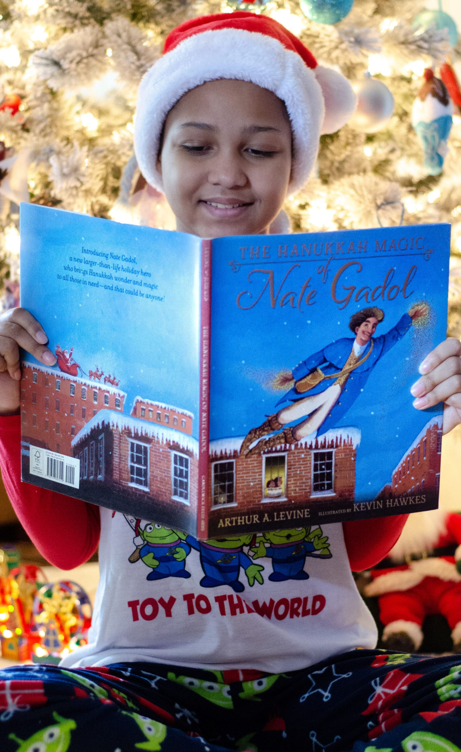 Keke Reading Hanukkah Magic of Nate Gadol. Give the gift of literature this holiday season! These wonderful holiday books for kids make great stocking stuffer gifts. Create your very own Christmas Tree Advent Calander using these Children's holiday books, simply stack them into a tree for a new fun holiday tradition.