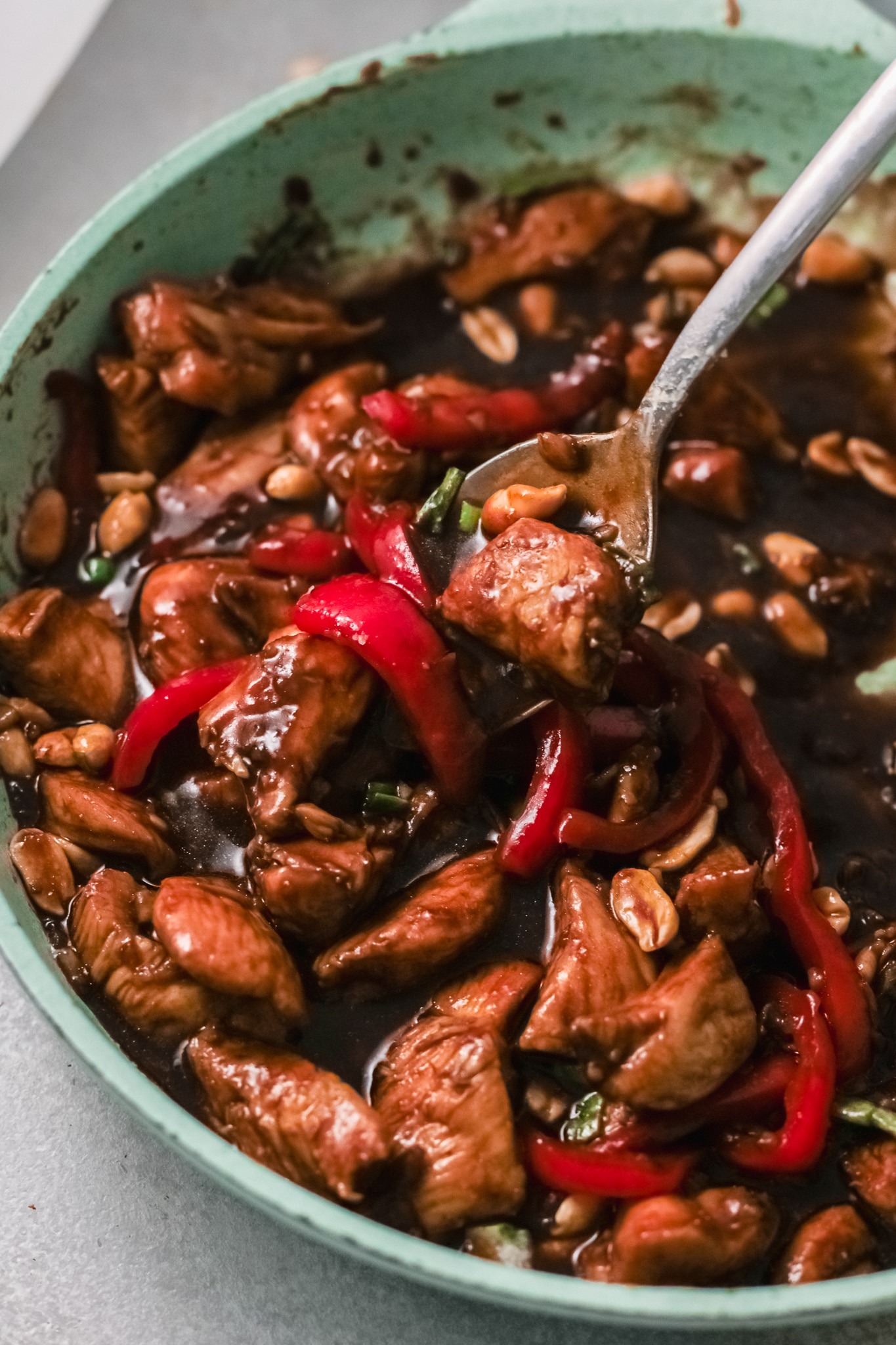 Better than Chinese takeout, make this Kung Pao Chicken at home. Closeup of the finished Kung Pao Chicken dish being scooped up with a large spoon.