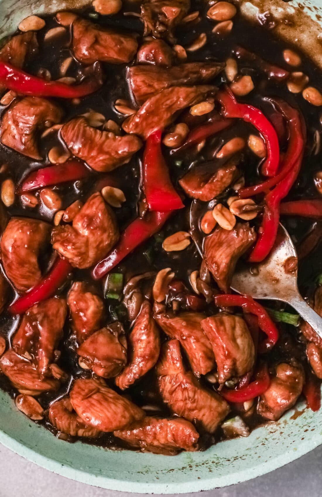 Better than Chinese takeout, make this Kung Pao Chicken at home. Upclose shot of the finished Kung Pao Chicken dish displaying the red bell peppers, chicken pieces in the savory sauce.