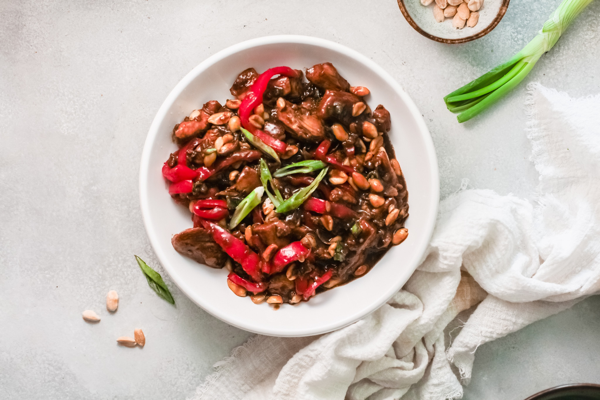 Better than Chinese takeout, make this Kung Pao Chicken at home. A horizonal shot of the Kung Pao Chicken dish being served in a white bowl next to a white napkin.