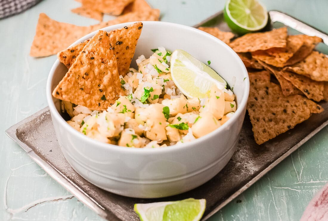Easy pineapple salsa dip in bowl with tortilla chips. On platter and ready to be served.