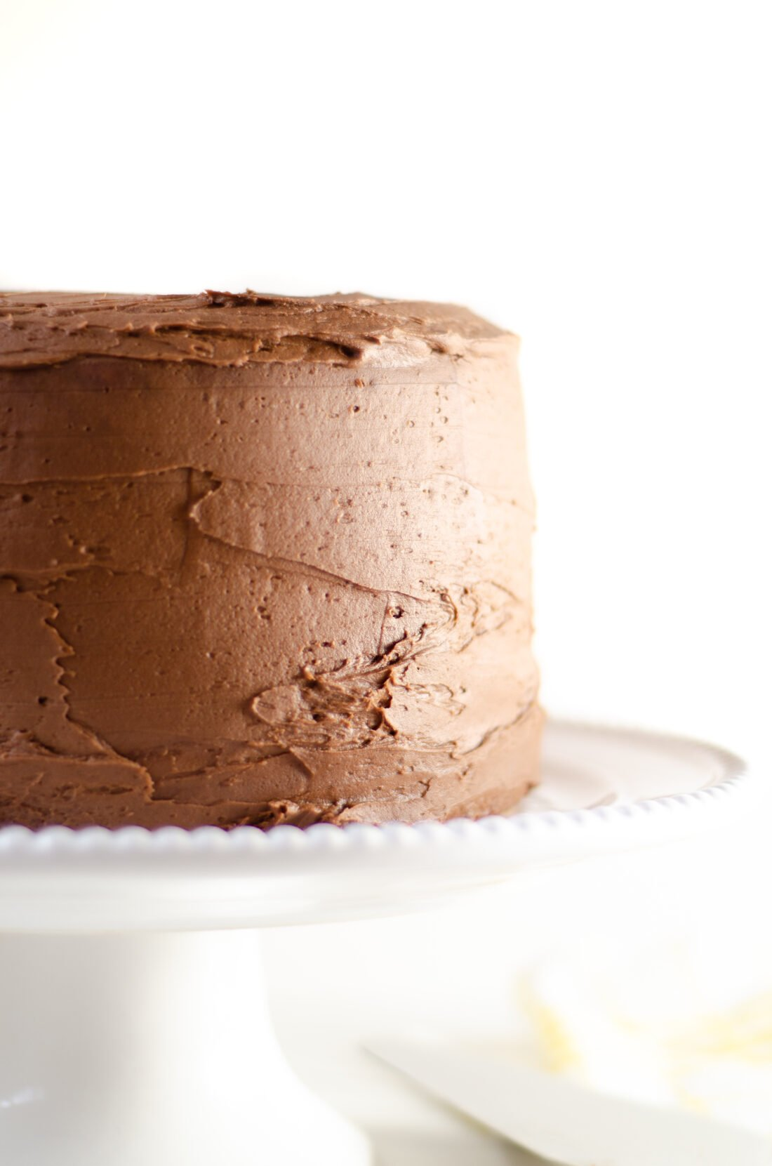 A classic homemade yellow butter cake recipe, with a homemade chocolate frosting. Bake this easy from scratch yellow cake recipe, topped with a smooth chocolate buttercream frosting for your next celebration.