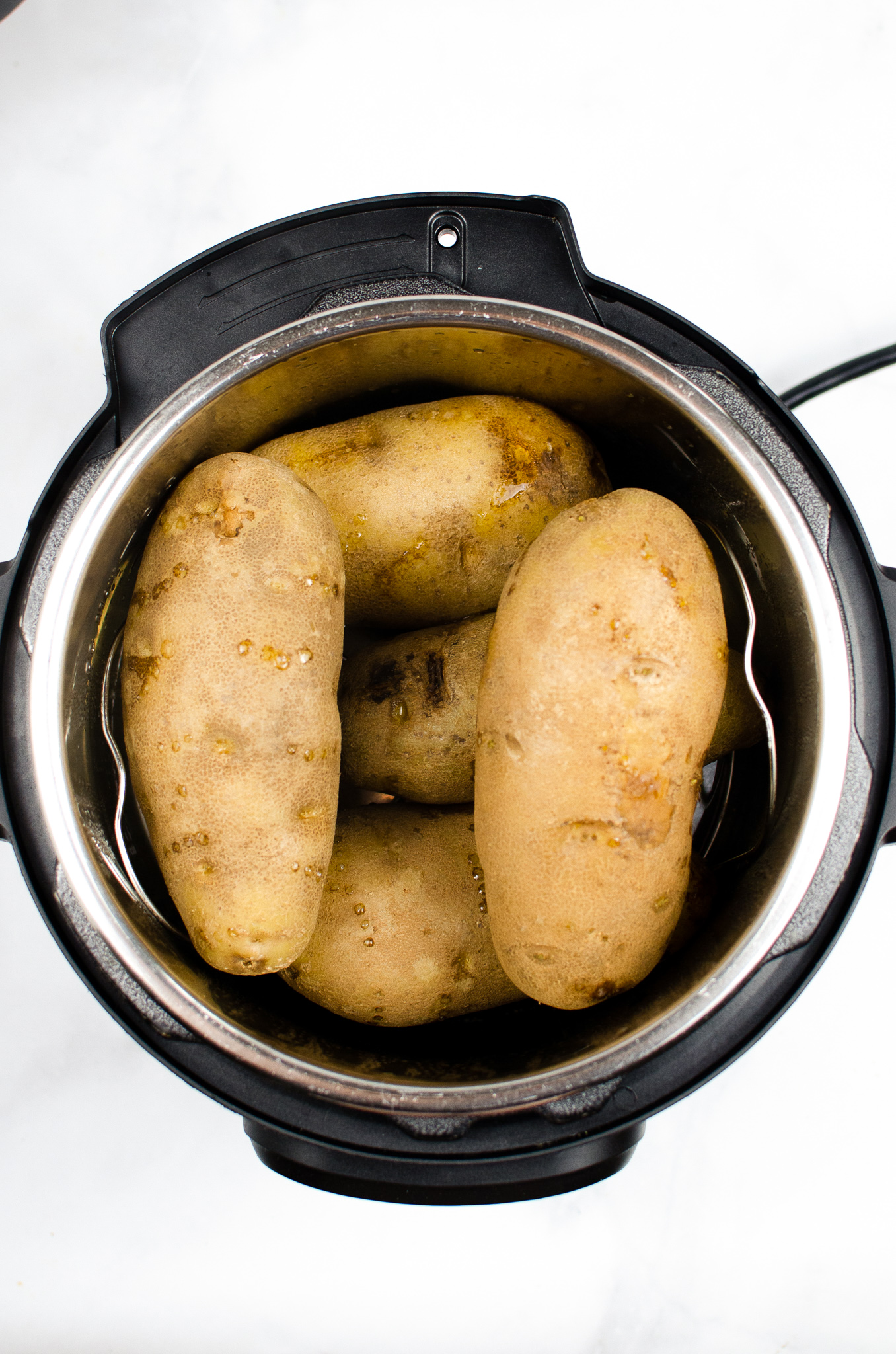 This foolproof recipe creates fluffy, fork-tender potatoes in half the time of the oven. Instant Pot Baked Potatoes use no foil and are great for busy nights. It's a pressure cooker recipe that's ready in just minutes.
