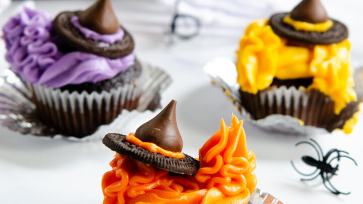 It's just a bunch of hocus pocus! Whip up these easy Hocus Pocus Cupcakes featuring the Sanderson Sisters for your next Halloween party. Just in time for the premiere of Hocus Pocus 2 in 2022, exclusively on Disney+. These Hocus Pocus Witch cupcakes are a fun and simple Halloween dessert recipe idea.